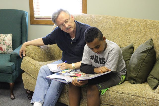 Volunteer reading with young boy at Community Kids program.