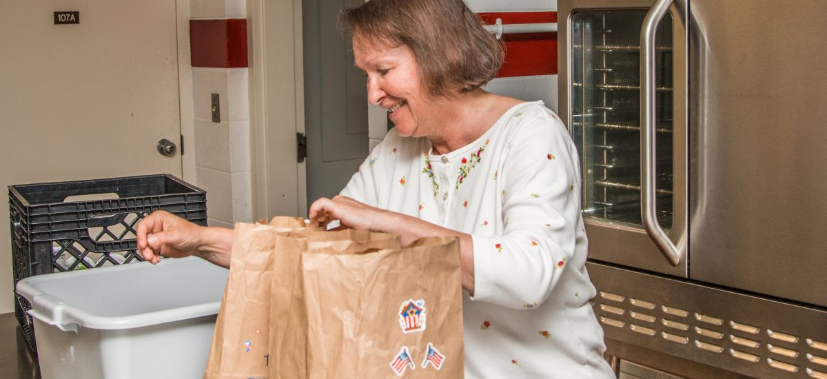 Staff member packing meals on wheels
