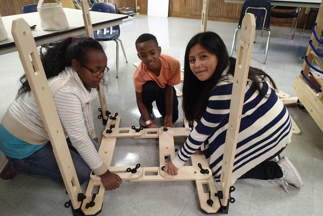 Students work together to build a machine in Community Kids Program.