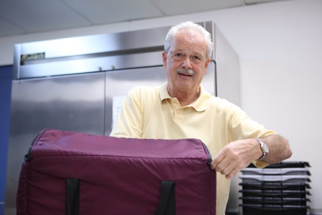 Man volunteering with Meals on Wheels
