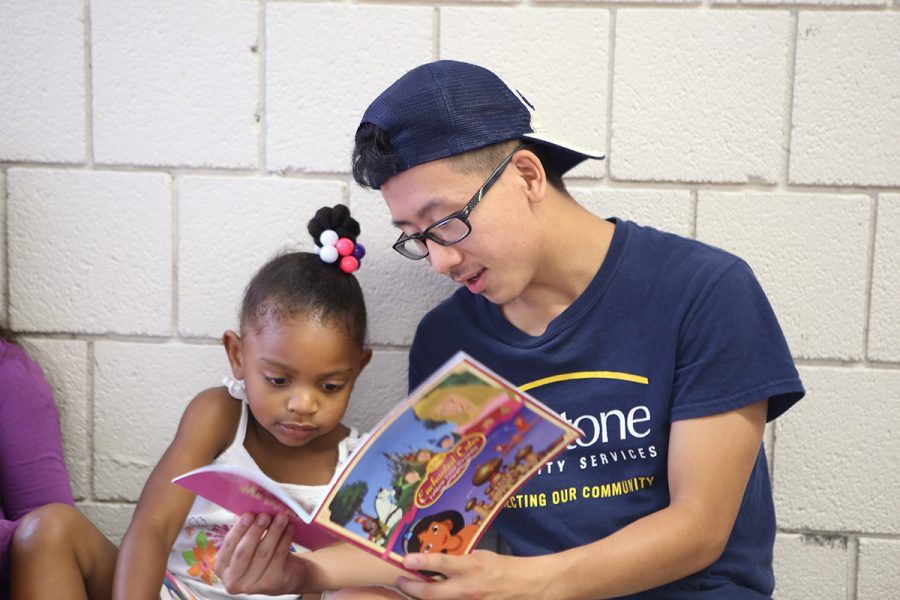 Young man helping little girl with reading
