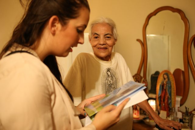 Volunteer reading card to senior