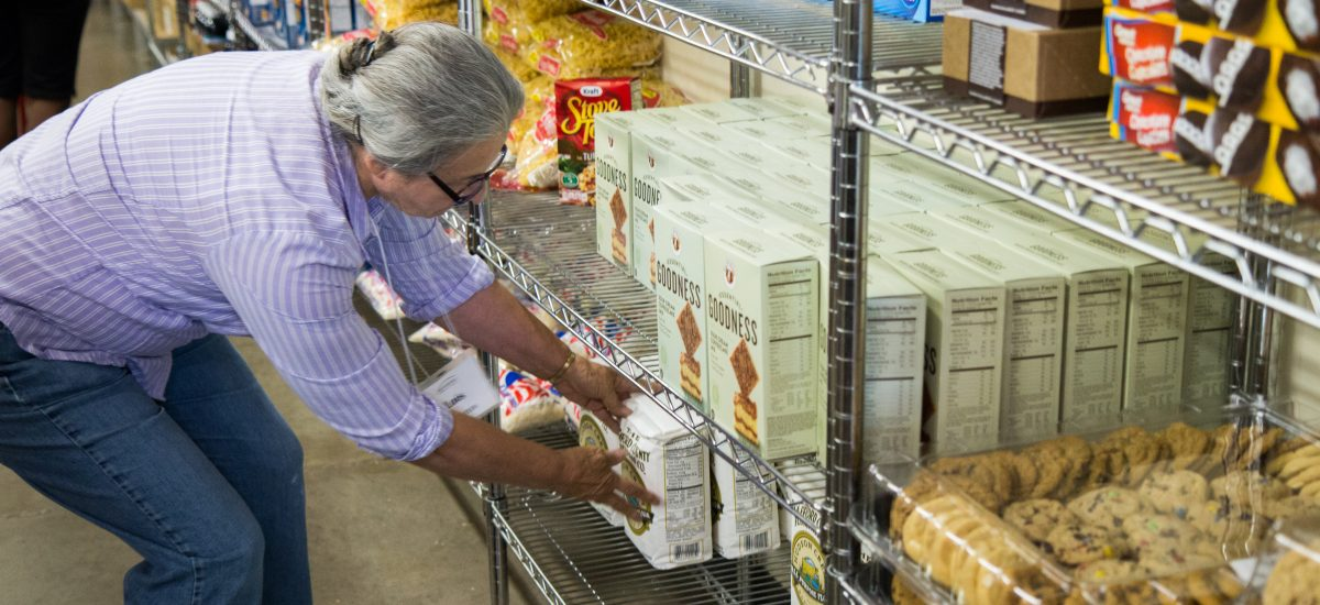 Volunteer stocking food at food shelf